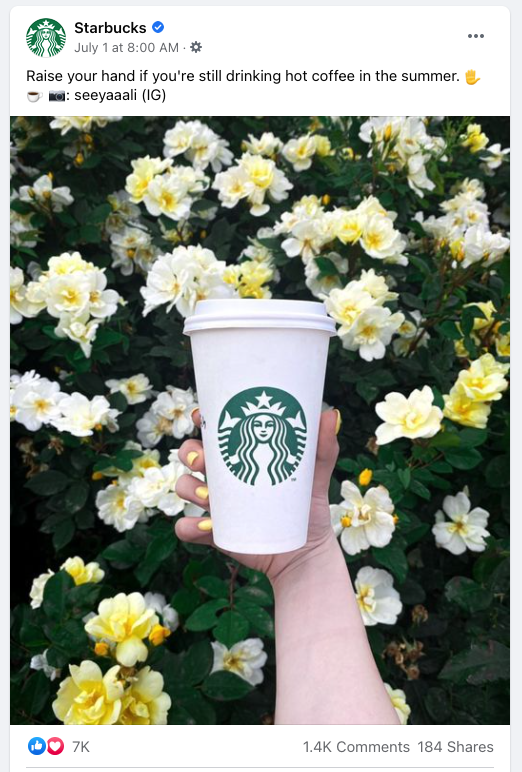 facebook post- hand holds starbucks cup in front of yellow and white flowers